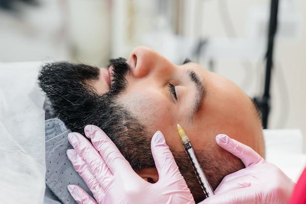 Procedimento cosmético para aumento dos lábios e remoção de rugas em um homem barbudo