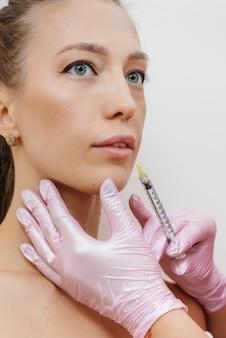 Procedimento de aumento dos lábios para uma linda jovem. cosmetologia.