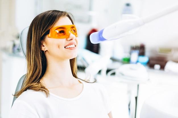 Procedimento de clareamento dos dentes para uma paciente feliz do sexo feminino em uma clínica odontológica.