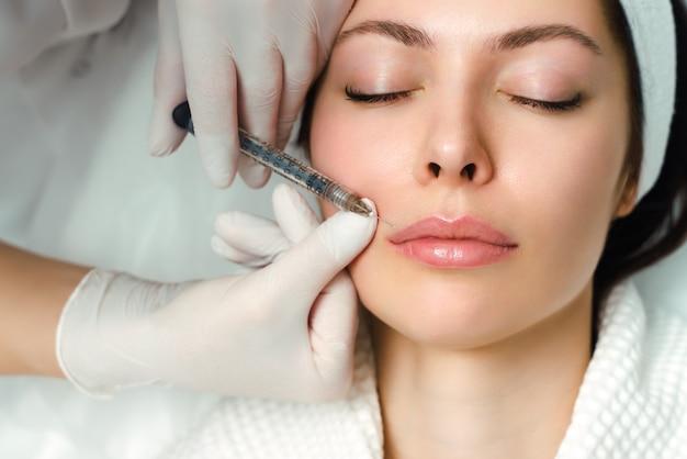 Procedimento de correção da forma labial em um salão de cosmetologia. o especialista faz uma injeção nos lábios do paciente. aumento de lábios.
