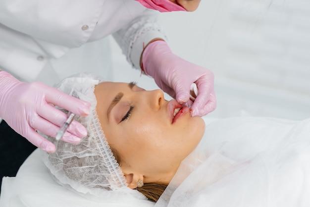 Procedimento de cosmetologia para aumento dos lábios e remoção de rugas em uma linda jovem. cosmetologia.