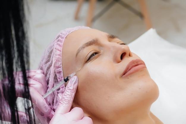 Procedimento de cosmetologia para aumento dos lábios e remoção de rugas em uma linda jovem. cosmetology.