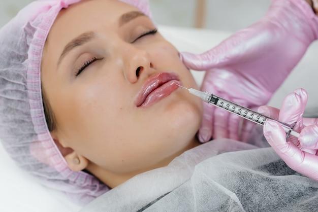 Procedimento de cosmetologia para aumento dos lábios e remoção de rugas em uma linda jovem