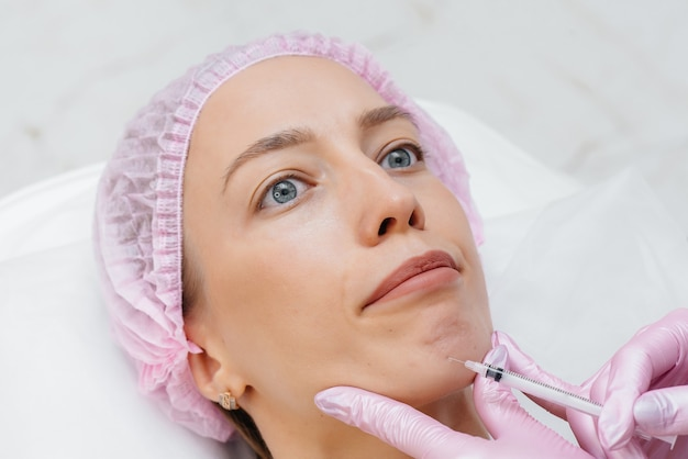 Procedimento de cosmetologia para aumento dos lábios e remoção de rugas para uma jovem e bela mulher