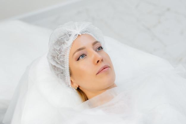 Procedimento de cosmetologia para aumento dos lábios e remoção de rugas para uma jovem mulher bonita