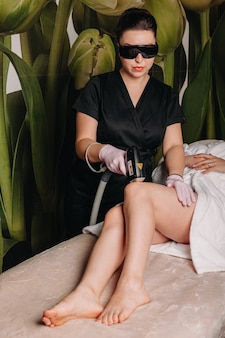 Procedimento de depilação a laser realizado em clínica dermatológica nas pernas femininas