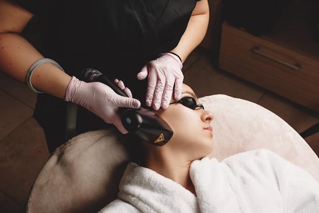 Procedimento de depilação facial feito no rosto da mulher com aparelho