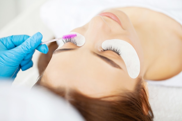 Procedimento de extensão de cílios, estilista profissional alongando cílios femininos