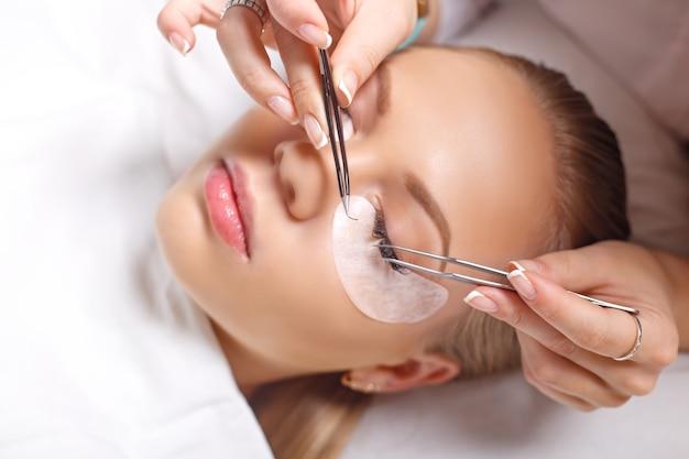 Procedimento de extensão de cílios. olho de mulher com cílios longos. cílios, close-up.