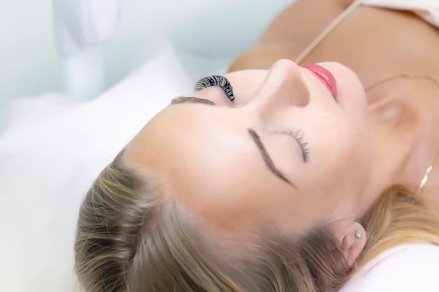 Procedimento de extensão de cílios. olho de mulher com cílios longos. fechar-se