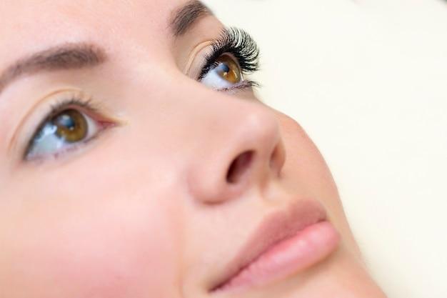 Procedimento de extensão de cílios. olho de mulher com cílios longos.