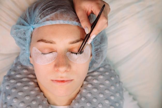 Procedimento de extensão dos cílios. olho de mulher com cílios longos. chicotes, fim acima, macro, foco seletivo.