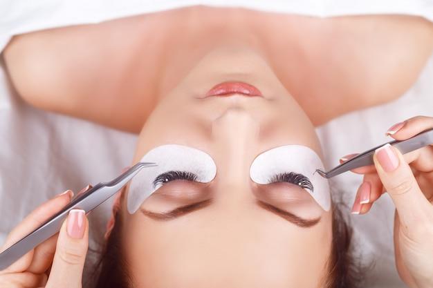 Procedimento de extensão dos cílios. olho de mulher com cílios longos. pestanas com strass. cílios, close-up
