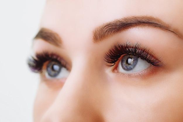 Procedimento de extensão dos cílios. olho de mulher com cílios longos