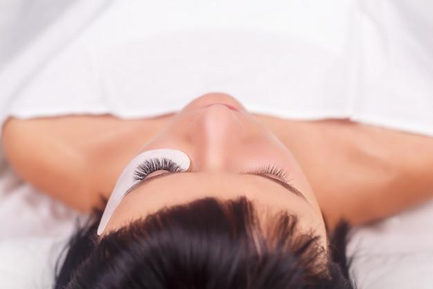 Procedimento de extensão dos cílios. olho de mulher com cílios longos.