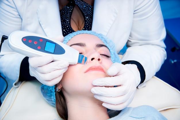 Procedimento de limpeza ultrassônica do rosto. purificador ultra-sônico. conceito de tratamento médico e cuidados com a pele.