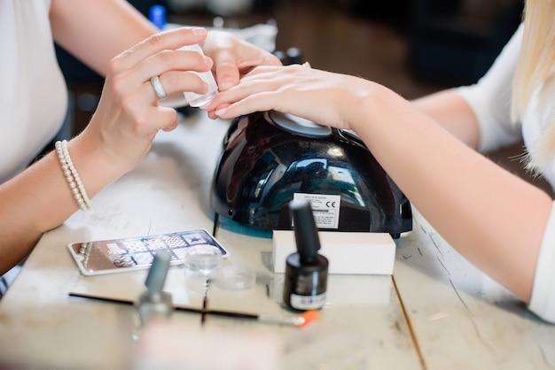 Procedimento de manicure com padrão e prata unhas polonês