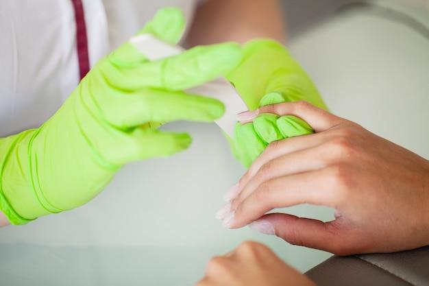 Procedimento de manicure. vista lateral do processo de manicure em salão de beleza
