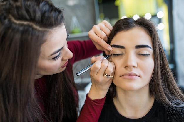 Procedimento de maquiagem das pálpebras para modelo sorridente de cabelos compridos no salão de beleza