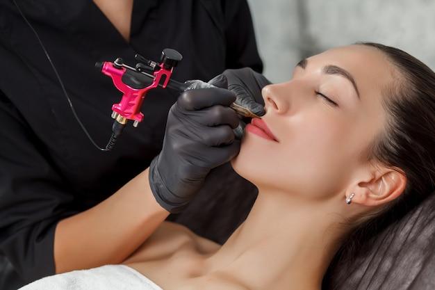 Procedimento de maquiagem permanente, aplicando-se em jovem. close-up.