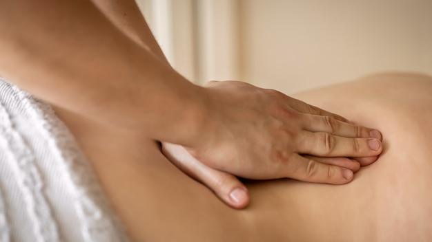 Procedimento de massagem, mãos do homem massagista realizando massagem nas costas, conceito de saúde