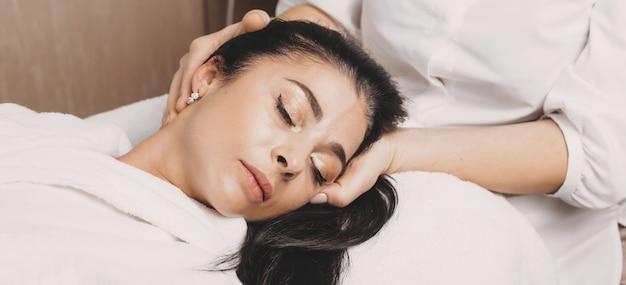 Procedimento de massagem na cabeça com uma senhora morena caucasiana, deitada no sofá no salão spa