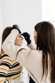 Procedimento de modelagem de sobrancelha, mestre de maquiagem modelando as sobrancelhas.