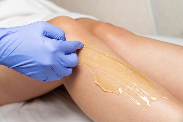 Procedimento de mudança de pé em um salão de beleza um mestre enluvado aplica pasta de açúcar na perna de uma mulher para depilação.