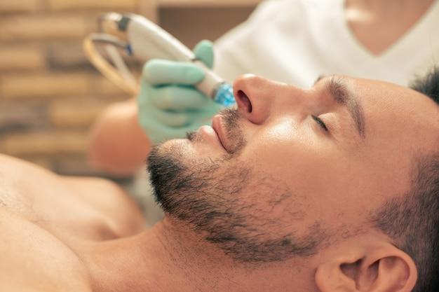 Procedimento de nutrição da pele do salão de beleza e jovem barbudo relaxando com os olhos fechados