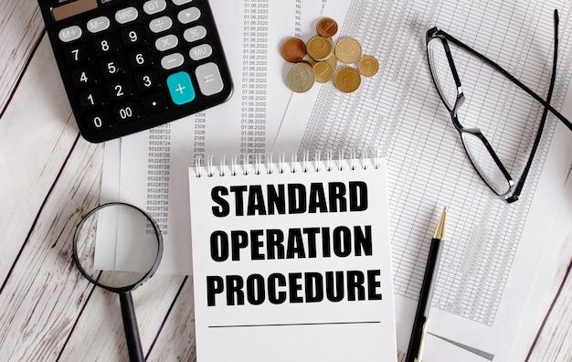 Procedimento de operação padrão escrito em um bloco de notas branco próximo a uma calculadora, dinheiro, óculos, uma lupa e uma caneta. conceito de negócios