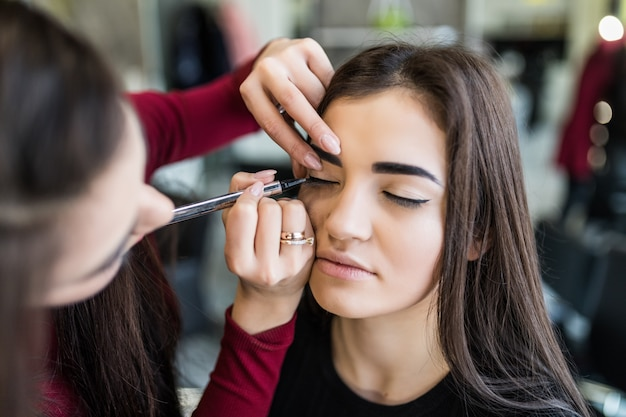 Procedimento de pálpebras para modelo bonito de cabelos compridos no salão de beleza