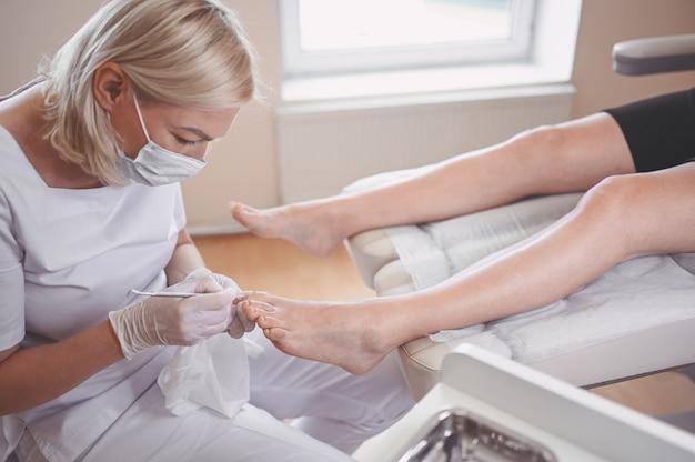 Procedimento de pedicure médico profissional close-up usando instrumento de unha dupla