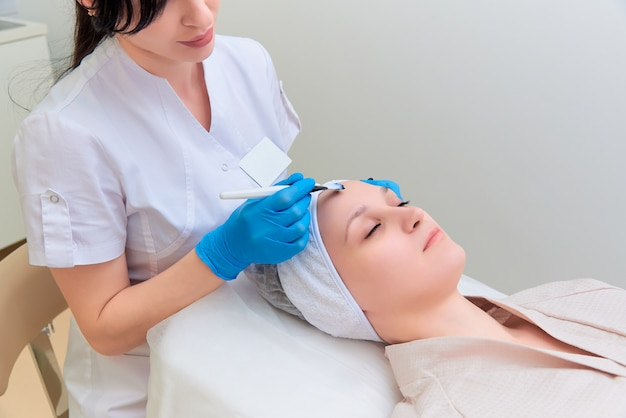 Procedimento de peeling facial com carbono na clínica de cosmetologia a laser.