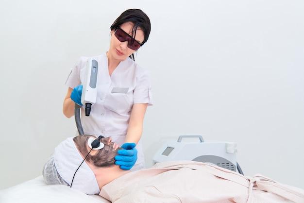 Procedimento de peeling facial de carbono na clínica de cosmetologia a laser.