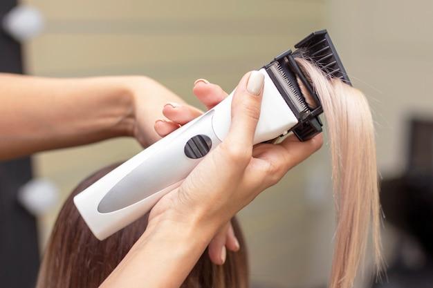 Procedimento de polimento de cabelos. o cabeleireiro no salão lustra o cabelo com uma máquina especial para polir o cabelo. cortando pontas duplas do cabelo. foto vertical