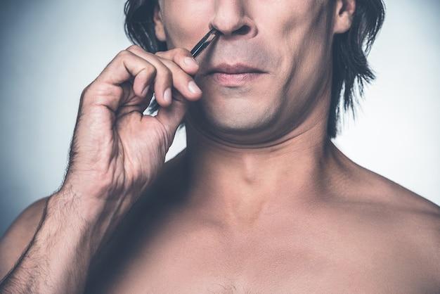 Procedimento doloroso. close de um jovem sem camisa arrancando o cabelo do nariz e fazendo uma careta em pé contra um fundo cinza
