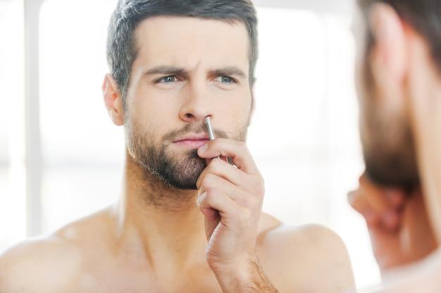 Procedimento doloroso. jovem concentrado tirando o cabelo do nariz e olhando para si mesmo em frente ao espelho