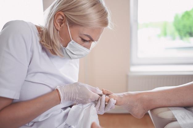 Procedimento médico profissional de pedicure close-up usando o instrumento cortador de unhas