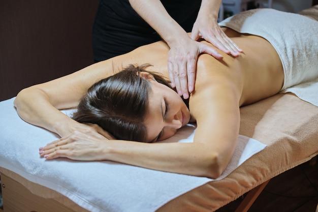 Procedimento profissional de massagem nas costas, mulher adulta recebendo tratamento deitada na mesa de massagem