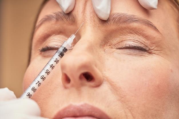 Procedimentos anti-envelhecimento fecham a cena da esteticista em luvas de proteção, fazendo injeção cosmética em