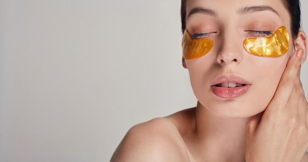 Procedimentos cosméticos. cuidados com a pele facial. jovem mulher bonita aplicando manchas de colágeno dourado sob ela os olhos. remova rugas e olheiras. uma mulher cuida de uma pele delicada ao redor dos olhos.