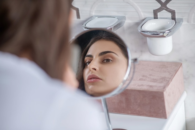 Procedimentos de beleza. uma linda mulher olhando para o pequeno espelho