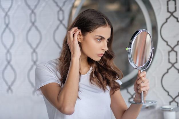 Procedimentos de beleza. uma mulher olhando para o pequeno espelho portátil