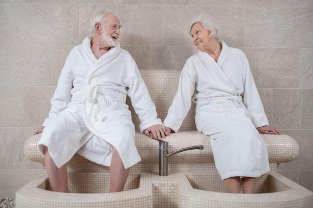 Procedimentos de spa. casal maduro em túnicas brancas fazendo hidromassagem para os pés e se sentindo bem