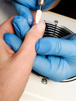 Processamento de unhas com manicure em um salão de beleza
