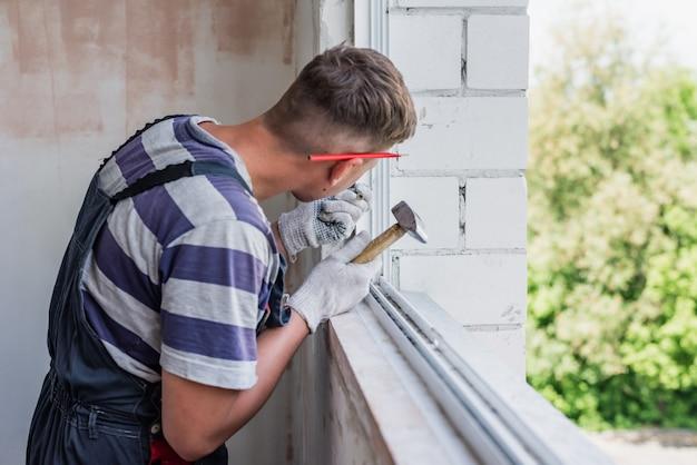 Processe o trabalhador masculino que repara a janela em uma casa, close-up
