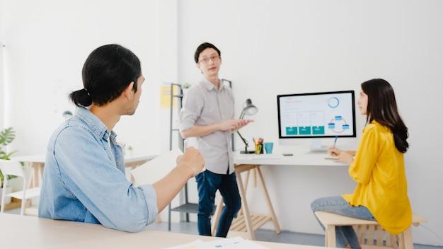 Processo colaborativo de empresários multiculturais usando apresentação em laptop e reunião de comunicação para brainstorming de idéias sobre novos colegas de projeto, trabalhando na estratégia de sucesso do plano de trabalho em casa.