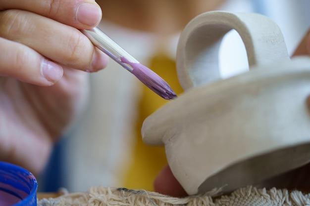 Processo criativo de criação de cerâmica em estúdio de oleiro com cerâmica feminina pintando utensílios de cozinha