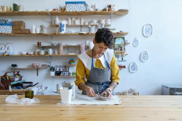 Processo criativo em estúdio de cerâmica jovem artista modelando escultura de argila para oleiro