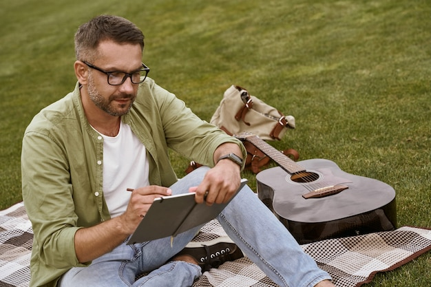 Processo criativo jovem focado em músico masculino usando óculos, sentado em uma grama verde